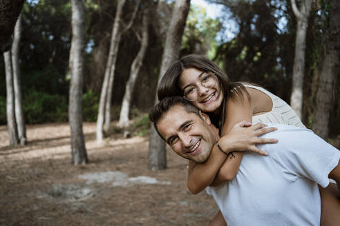 Happy father giving piggyback to daughter in forest - RCPF00397