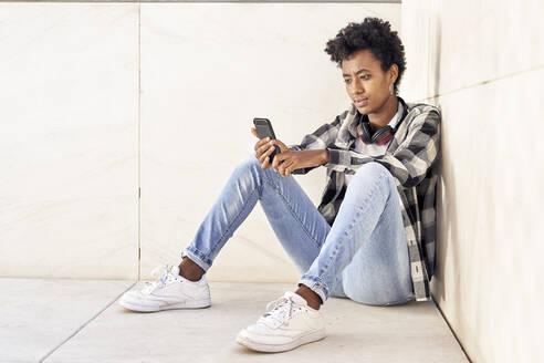 Beautiful Afro woman using smart phone against retaining wall - VEGF03146