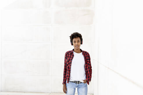Confident young Afro woman listening music while standing with hand in pocket against white wall - VEGF03170
