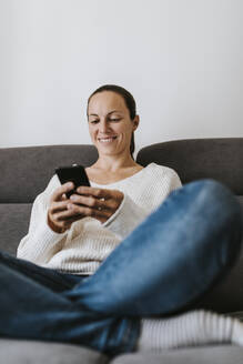 Happy woman using phone on sofa at home - DMGF00334