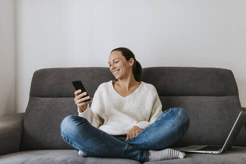 Smiling woman using smart phone while sitting with laptop on sofa - DMGF00337