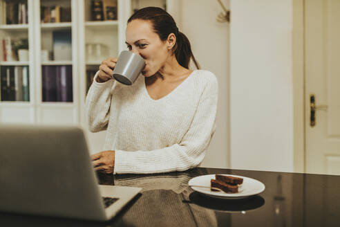 Woman drinking coffee while looking at laptop in illuminated kitchen - DMGF00349