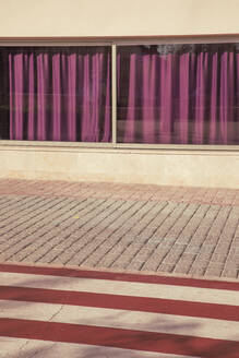 Purple curtains covering windows overlooking zebra crossing and empty sidewalk - JMF00528