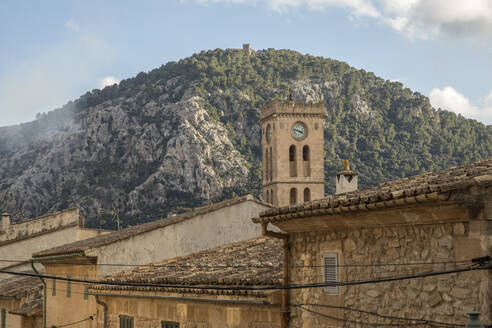 Spain, Mallorca, Pollenca, Bell tower rising over old town houses with mountain in background - JMF00546