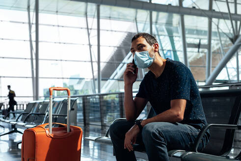 Young man wearing a face mask talking on the phone at the airport - CAVF91206