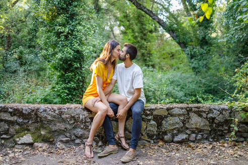 Full body of young stylish couple in casual clothes kissing while sitting on stone border against lush green trees in summer park - ADSF18074