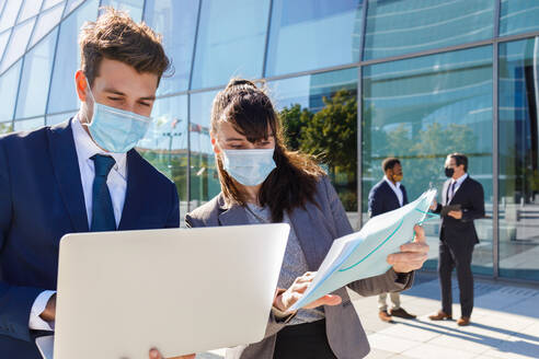 Unrecognizable young man and woman in formal suits and medical masks examining documents while working together on street using laptop near modern business building - ADSF18080
