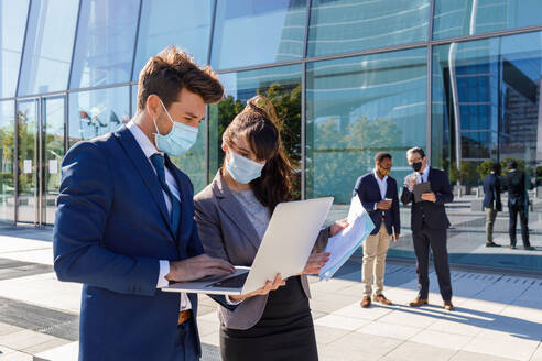Unrecognizable young man and woman in formal suits and medical masks examining documents while working together on street using laptop near modern business building - ADSF18083
