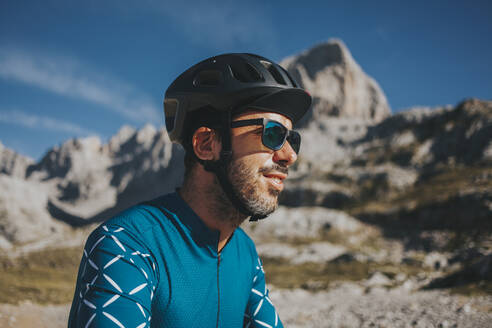 Cyclist wearing sunglasses and cycling helmet at Picos de Europa National Park on sunny day, Cantabria, Spain - DMGF00356