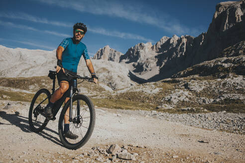 Mountain cyclist with bicycle exploring Picos de Europa National Park, Cantabria, Spain - DMGF00359
