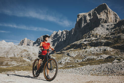 Adventurous cyclist looking away at Picos de Europa National Park during weekend, Cantabria, Spain - DMGF00368
