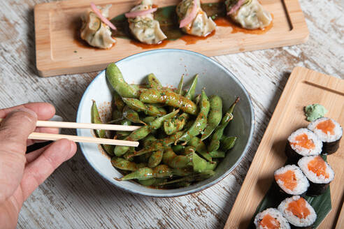 From above of bowl with edamame soy beans in pods served on wooden table with sushi rolls and boiled gyoza dumplings - ADSF18206