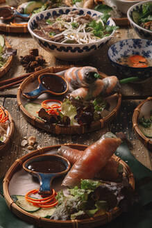 From above of assorted dishes of Vietnamese cuisine arranged on wooden table in luxury restaurant - ADSF18209