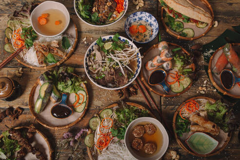 Top view of assorted dishes of Vietnamese cuisine arranged on wooden table in luxury restaurant - ADSF18212
