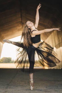 Elegant ballerina with eyes closed in black tutu and pointe shoes balancing on leg while moving gracefully during rehearsal in passage in city - ADSF18242