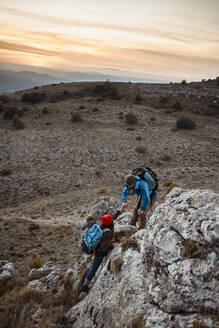 Boyfriend helping girlfriend to climb rock on mountain during sunset - RCPF00434