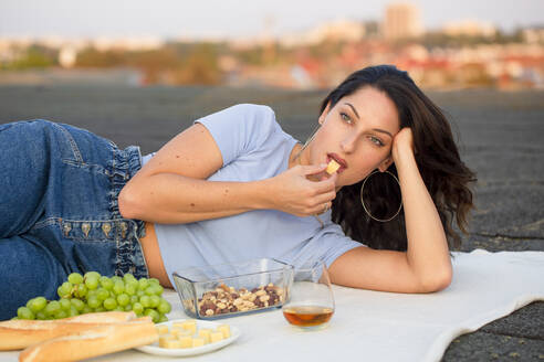 Beautiful woman eating cheese, lying on rooftop at picnic - NGF00721
