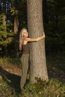 Mature woman hugging tree at park - FCF01931