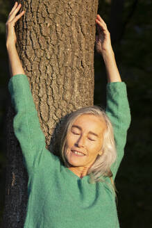 Mature woman with eyes closed against tree trunk at park during autumn - FCF01940