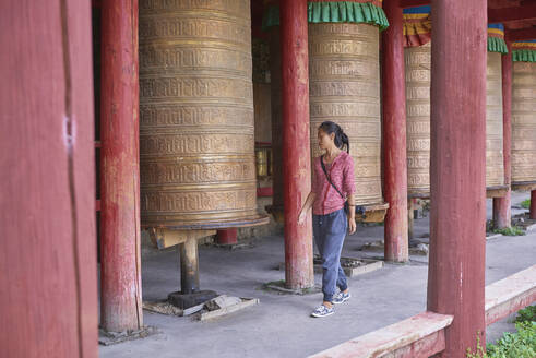 Full body of Asian female passing by Tibetan rolls with ancient prayer near sacred oriental temple - ADSF18317