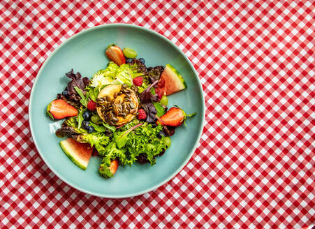 Overhead of goat roller cheese salad served on plate with various fruits and fresh greenery on table in cafe - ADSF18350