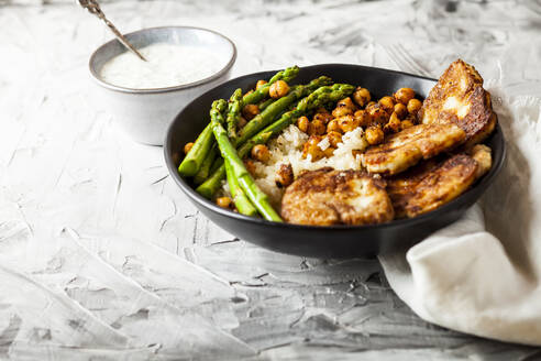 Dipping sauce and bowl of rice with chick-peas, asparagus stalks and friedhalloumicheese - SBDF04431