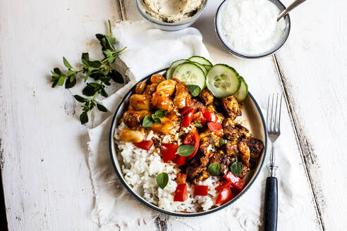 Bowl of Greek gyro with rice, fava beans, halloumi cheese, tomatoes and cucumbers - SBDF04440