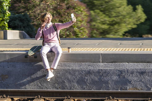 Smiling man gesturing peace sign while taking selfie sitting with longboard on station platform - GGGF00224