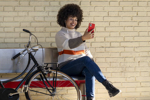 Happy woman taking selfie while sitting on bench by bicycle against brick wall - GGGF00242