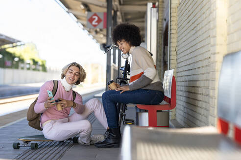 Young man sharing smart phone with female friend while sitting at railroad station - GGGF00248