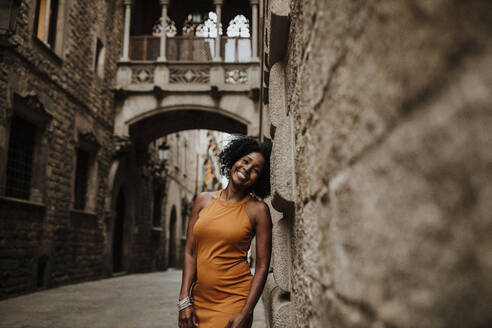Smiling woman leaning on wall, Barcelona, Spain - GMLF00878