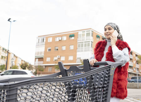 Woman talking on mobile phone while standing with shopping cart at city - JCCMF00066