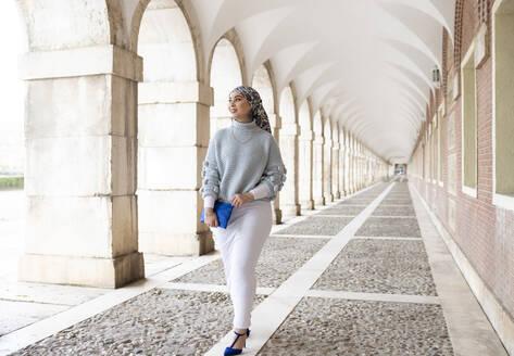 Smiling woman looking away while walking at corridor - JCCMF00075