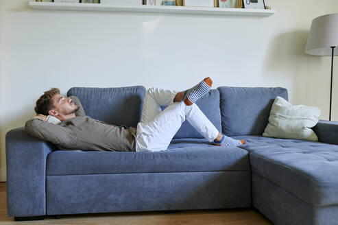 Man resting on sofa with hands behind head in living room at home - KIJF03422