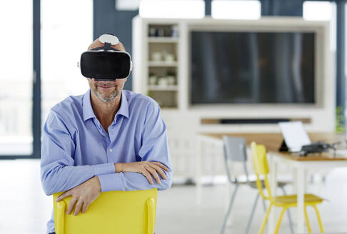 Smiling businessman using virtual reality headset while leaning on chair at home - FMKF06760