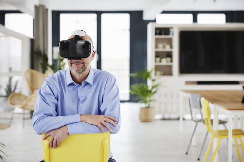 Smiling businessman using virtual reality headset while sitting on chair at home - FMKF06823