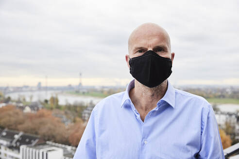 Mature businessman wearing protective face mask standing on rooftop - FMKF06832