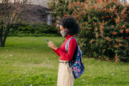 Student wearing headphones and protective face mask using smart phone while standing outdoors - MARF00006