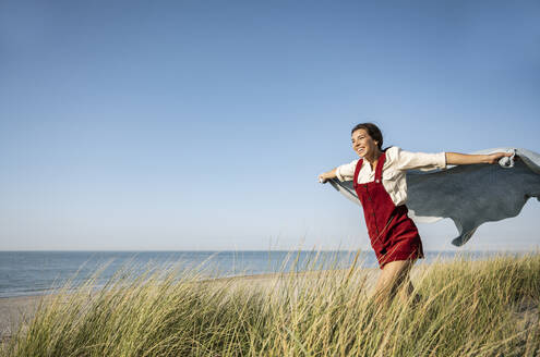 Carefree woman holding shawl while running on beach during sunny day - UUF22231