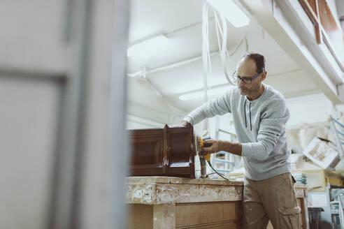 Craftsman using sander on furniture while standing at workshop - OCAF00578