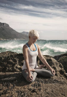 Blond woman meditating while practicing lotus position yoga on rock formation at beach - AJOF00894