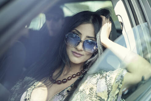 Beautiful young woman with hand in hair sitting in car - AJOF00915