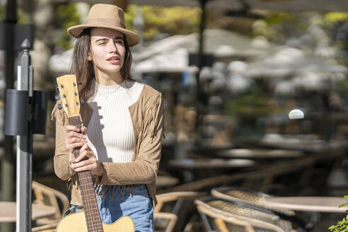 Thoughtful young woman with guitar standing during sunny day - GGGF00257