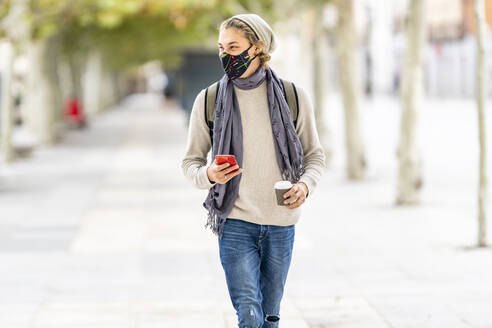 Young man with wearing face mask using mobile phone while walking in city - GGGF00317