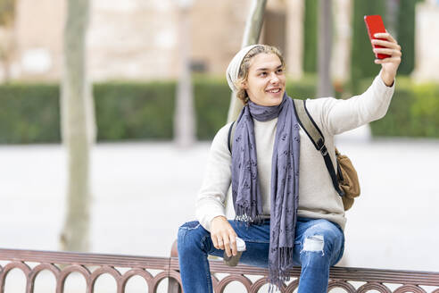 Young man taking selfie through mobile phone while sitting on railing in city - GGGF00323
