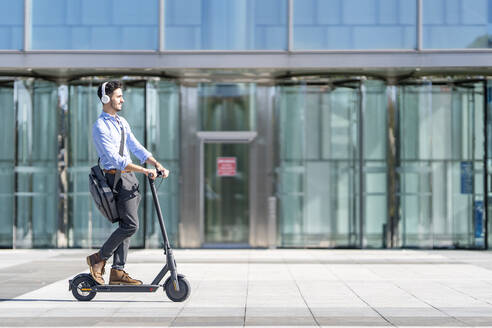 Young businessman wearing headphones riding push scooter on footpath - GGGF00371