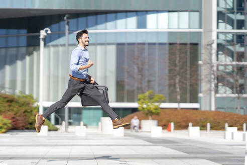 Happy businessman cheering while running on footpath - GGGF00374