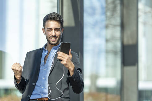 Smiling businessman wearing in-ear headphones cheering while using mobile phone standing outdoors - GGGF00377