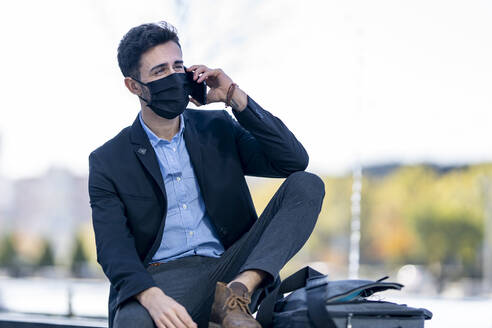 Businessman wearing protective face mask talking on mobile phone while sitting outdoors - GGGF00383