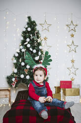 Cute boy wearing horned headband sitting against Christmas tree at home during Christmas - EBBF01695